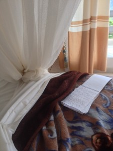 Notebook on my bed beside my mosquito net at Credo Hotel Butare Rwanda