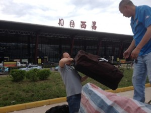 Bruce Lee struggles with my long bag at Xi Chang airport.